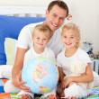 Cute children and their father looking at a terrestrial globe — Stock Photo