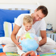 Laughing father and his son looking at a terrestrial globe — Stock Photo #10294925