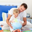 Enthusiastic father and his son looking at a terrestrial globe — Stock Photo #10294927