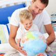 Merry father and his son looking at a terrestrial globe — Stock Photo