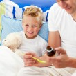 Smiling father giving cough syrup to his sick son — Stock Photo