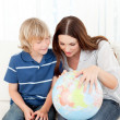 Interested child looking at a terrestrial globe with his mother — Stock Photo