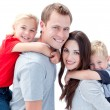 Portrait of joyful family enjoying piggyback ride against a whit — Stock Photo #10295002