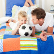 Stock Photo: Adorable little boy and his father watching a football match