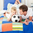 Adorable little boy and his father watching a football match — Stock Photo