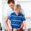 Stock Photo: Loving father helping his son prepare breakfast