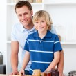 Stock Photo: Smiling father helping his son prepare breakfast