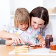 Stock Photo: Brunette mother helping her daughter prepare breakfast