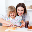 Stock Photo: Attentive mother helping her daughter prepare breakfast