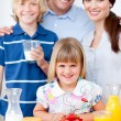Joyful family eating breakfast in the kitchen — Stock Photo