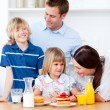 Stock Photo: Jolly family eating breakfast in the kitchen