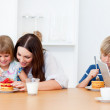 Merry family eating breakfast in the kitchen — Stock Photo