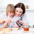Adorable little girl and her mother preparing toasts — Stock Photo #10295051