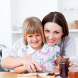Cute little girl and her mother preparing toasts — Stock Photo