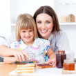 Blond little girl and her mother preparing toasts — Stock Photo #10295055