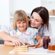 Smiling little girl and her mother preparing toasts — Stock Photo