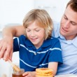 Adorable boy and his father putting honey on waffles — Stock Photo #10295081