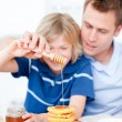 Smiling boy and his father putting honey on waffles — Stock Photo