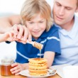 Adorable boy and his father putting honey on waffles — Stock Photo