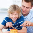 Attentive father and his son eating waffles — Stock Photo