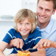 Stock Photo: Smiling father and his son eating waffles
