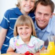 Happy family eating waffles with strawberries — Stock Photo