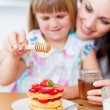 Cute little girl and her mother putting honey on waffles — Stock Photo