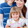 Cheerful mother and her children eating waffles with strawberrie — Stock Photo