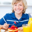 Jolly boy eating waffles with strawberries — Stock Photo