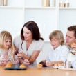 Cheerful family eating muffins in the kitchen — Stock Photo #10295122