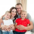Stock Photo: Portrait of Happy family sitting on sofa