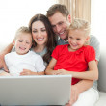 Joyful family using a computer sitting on sofa — Stock Photo