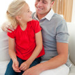 Adorable little girl sitting on sofa with her father — Stock Photo