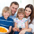 Royalty-Free Stock Photo: Portrait of a smiling family eating crisps while watching TV