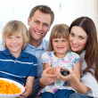 Happy family watching television and eating chips — Stock Photo