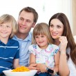 Family watching television and eating chips — Stock Photo