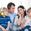 Family listening music with headphones — Stock Photo