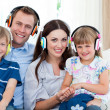 Smiling family listening music with headphones — Stockfoto