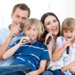 Happy family singing a karaoke together — Stock Photo #10295181