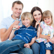 Smiling young family singing a karaoke together — Stock Photo