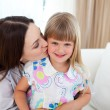 Attentive mother kissing her little girl — Stock Photo #10295199