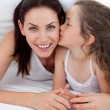 Little girl kissing her mother lying on bed — Stock Photo #10295222