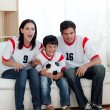 Parents and their son watching football match — Stock Photo #10295259
