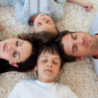 Family sleeping on the floor with heads together — Stock Photo