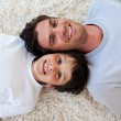 Smiling Father and his son lying on the floor — Stock Photo #10295286
