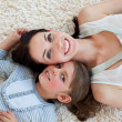 Stock Photo: Happy little girl and her mother lying on the floor
