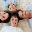 Happy family lying on the floor — Stock Photo #10295298