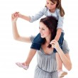 Merry mother giving her daughter piggyback ride — Stock Photo