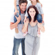 Smiling parents giving their children piggyback ride — Stock Photo