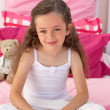 Little girl sitting on bed — Stock Photo